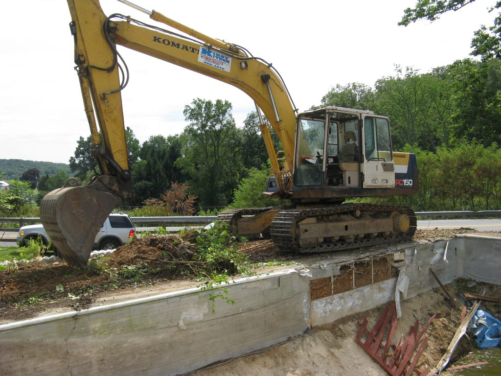 Removing inground pool with excavator